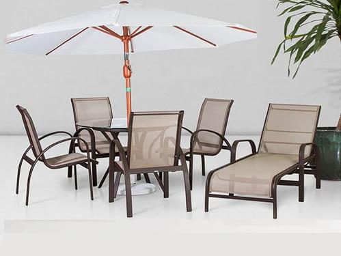 Um conjunto em tela sling com mesa e cadeira e ombrelone mais uma chaise